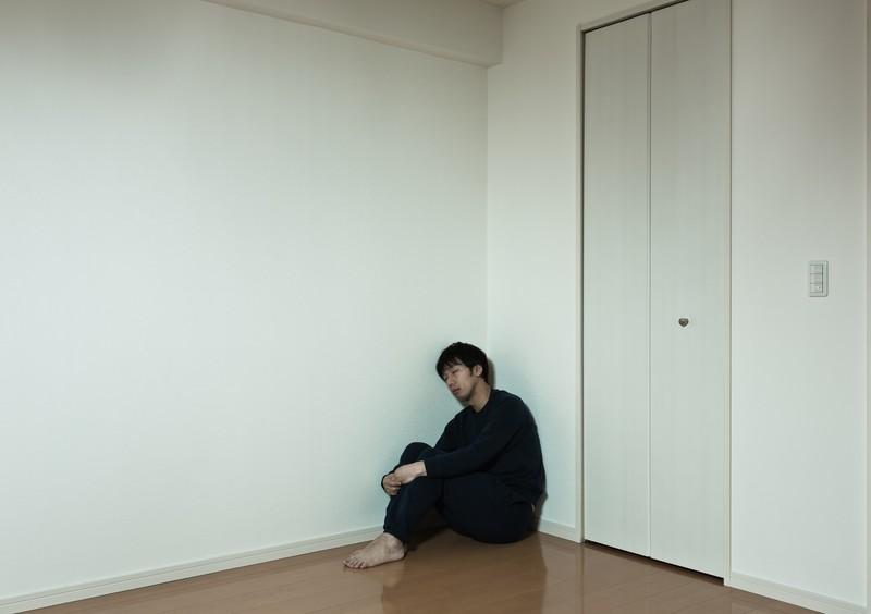 部屋の隅っこで独り寂しく寝落ちする男性の写真 https://www.pakutaso.com/20140306085post-3994.html